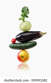 A stack of fruit and vegetables: eggplant, cucumber, apple, kohlrabi and radish.