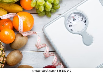Stack of fruits, white weight scale and tailor meter on wooden board. Concept of diet and healthy lifestyle