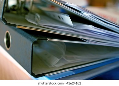 The stack of full ring binder files. Shallow DOF
