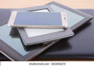 Stack of gadgets on a desk - notebook, tablet, ebook reader and a smatphone