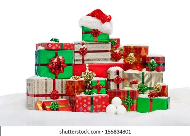 A stack of gift wrapped Christmas presents on snow, isolated against a white background.