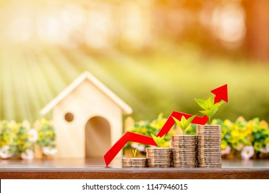 Stack gold coin with plant on the top and red arrow graph with growing value and wooden house put on the table in the public park, Business investment or loan for real estate concept.
