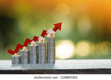Stack gold coin and a red arrow graph with growing value and wooden home model put on the top in the public park, Fund of real estate concept.