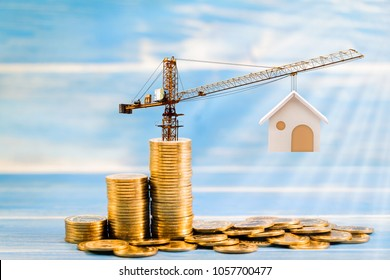 Stack gold coins with increase and tower crane and hoist brake solutions with build new house on the wood vintage blue background, saving money and loan for construction real estate and home concept.