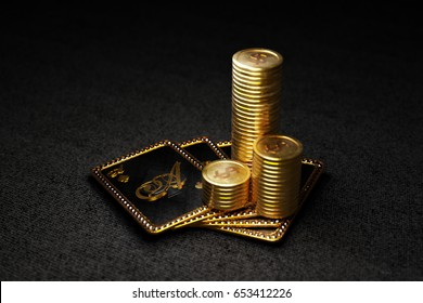 Stack of gold coins on royal poker cards on ace of spades. 3D illustration on black background.