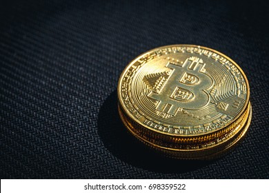 Stack of golden Bitcoin coins on black, toned copy space