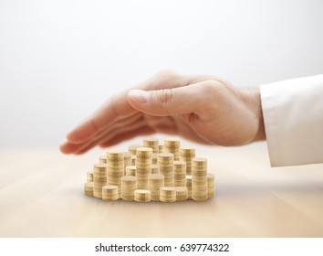 Stack of golden coins covered by hand. Savings protection concept