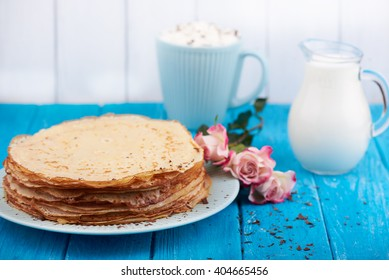 Stack of golden delicious pancakes, coffee, rose, romantic breakfast. On a blue wooden background. Selective focus