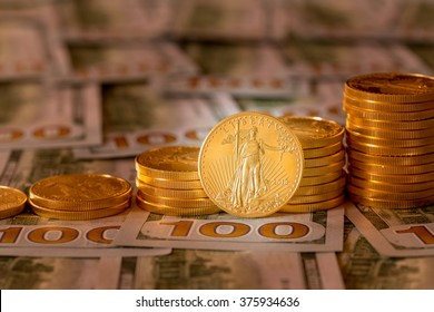 Stack of golden eagle coins on new design of US currency one hundred dollar bills with spotlight on the Liberty statue on one coin and warming color in the background