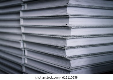 Stack of gray books on a bookshelf in the library. Front view. Education concept.