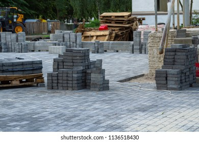 Stack of gray paving slabs. Laying the sidewalk of the tiles. Construction of sidewalks. Building materials for the construction of the sidewalk.