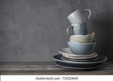Stack of grey crockery on rustic wooden table against shabby gray wall. Various plates, dish, bowls and mugs.