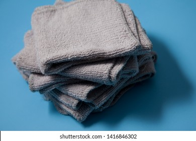 A stack of grey washcloths in a pile, clean and ready for use against a blue background