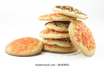 A stack of Halloween Sugar Cookies decorated with orange, brown, and yellow, sprinkles, isolated on white background, horizontal with copy space