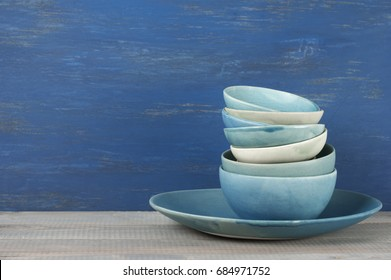 Stack of handmade blue ceramic bowls and dish on rustic wooden table against blue painted wooden wall.