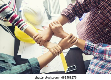 Stack hands of business engineering teamwork join together,construction engineer working in construction site, construction engineer conceptual,architect drawing on architectural project on background