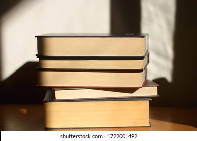 Stack of hard cover books, illuminated by sunlight. Selective focus.