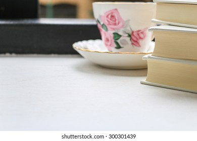 Stack of hardback books and a cup of tea in a vintage china cup and saucer on a windowsill. Selective focus.