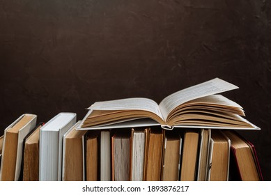 a stack of hardcover books on a dark background copy space