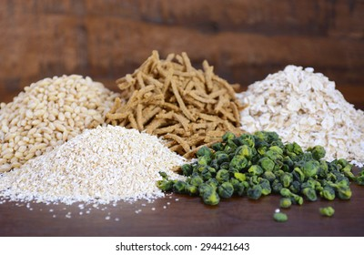 Stack of Healthy High Fiber Prebiotic Grains including wheat bran cereal, oat flakes and pearl barley, on rustic dark wood table background.