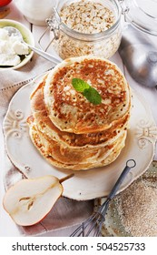 Stack of healthy low carb oat pancakes, jam and cream for breakfast over white wooden background