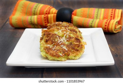 A stack of healthy, organic zucchini fritters on a white plate on a rustic tabletop.