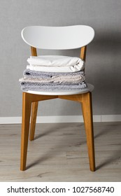 Stack of home linen on the chair in scandinavian style. Domestic cleaning.