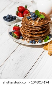 stack of homemade delicious pancakes for breakfast on white table, top view