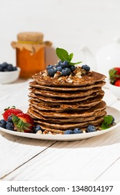 stack of homemade delicious pancakes for breakfast on white table, vertical closeup