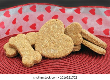 A stack of homemade dog biscuits, bone and heart shaped, in front of a festive Valentine's Day ribbon.