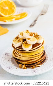 Stack of homemade pancakes with banana, maple syrup and walnuts on vintage plate. Fork, fresh sliced lemon, white and gray concrete background.