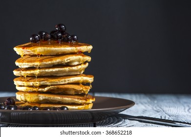 Stack of homemade pancakes with berries and honey on brown plate on rustic background. Russian holiday pancake week. Focus on pancakes. Horizontal view.