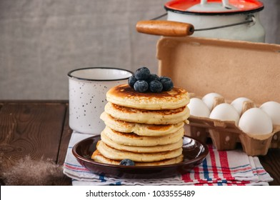 Stack of homemade pancakes with blueberries in a plate, milk in a flask, eggs in a paper container. Rustic style, still life. Copy space.