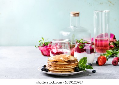 Stack of homemade pancakes served on plate with berries, mint, glass jars of yogurt, bottle of lemonade, fruit salad in pink dragon fruit over grey texture table. Copy space