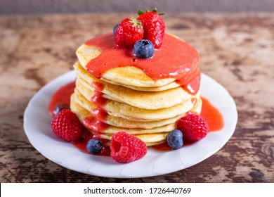 Stack of homemade pancakes with syrup and berries