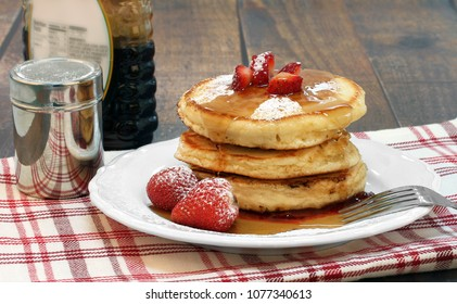 A stack of homemade pancakes topped with powdered sugar, fresh strawberries and maple syrup on a rustic table.