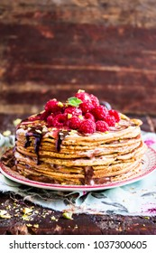Stack of homemade thin pancakes or crepes or pancake cake with chocolate sauce, fresh raspberry, pistachios nuts decorated with fresh mint leaves on a plate, selective focus