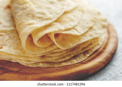 Stack of homemade wheat flour tortilla wraps for burrito close-up on wooden cutting board.