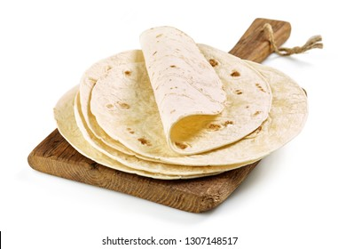 Stack of homemade wheat flour tortilla on wooden cutting board isolated on white background