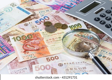 Stack of Hong Kong Dollar or banknotes with magnifying glass and calculator