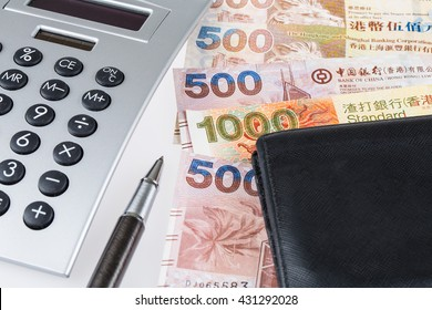 Stack of Hong Kong Dollar or banknotes with calculator, pen and black leather wallet conceptual