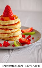 Stack of hot flapjacks served with fresh strawberries and kiwi