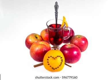 Stack of hot mulled wine with apples and oranges, cloves and vanilla sticks on a white background. Hot Christmas drink.