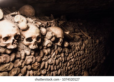 stack of human bones and skulls in the catacombes of paris as sy