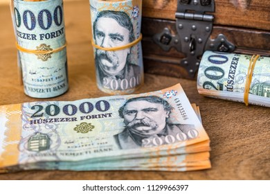 Stack of Hungarian money (forint) and rolled up 20000 forint banknotes with a closed vintage wooden box in the background