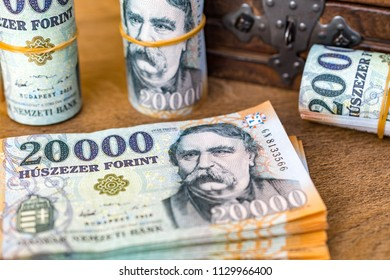 Stack of Hungarian money (forint) and rolled up 20000 forint banknotes with a vintage wooden box in the background