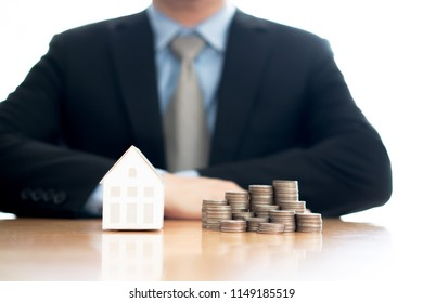 Stack of increasing coins and house model with businessman crossing his arms