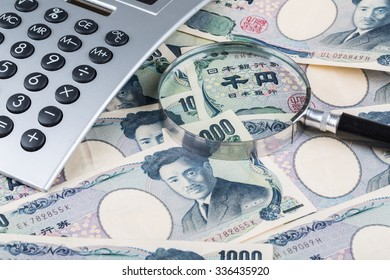 Stack of Japanese currency yen or Japanese banknotes with magnifying glass and calculator