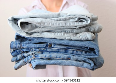 Stack of jeans in female hands.