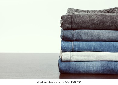 Stack of jeans on wooden background with empty space, vintage tone image